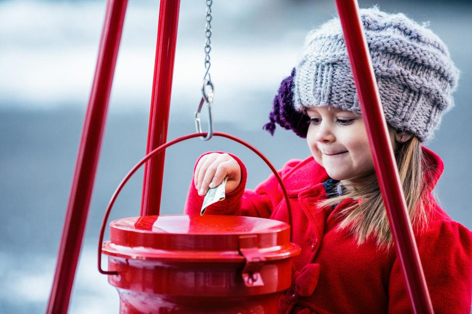 Little girl putting money in kettle